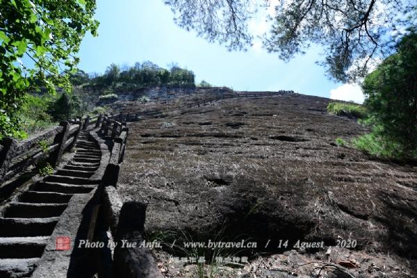 """好汉坡因毛泽东一句""""不到长城非好汉""""而得名。 进入虎啸岩景区向前走即遇到一个双岔口,直走是一条种植武夷岩茶的坡地,按照箭头指示向另一条路走去,往上看,是一巨大直耸云宵的山峰,自下而上呈""""之""""字型的台阶,倾斜度在六七十度之间,阶梯狭窄,迂回曲折,有时需要手脚并用爬过此坡,拾级而上,犹如在爬一座天梯。此天梯即为好汉坡。"""